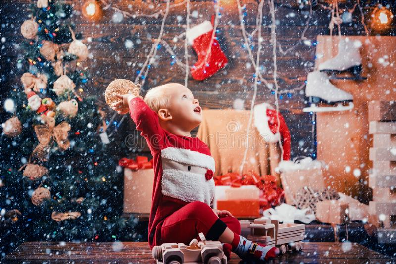 Happy child with a Christmas present on wooden background. Happy small kids in santa hat with present have a christmas stock images