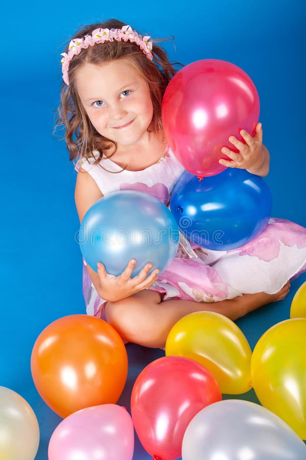 Happy child with colorful air ballons over blue royalty free stock photography