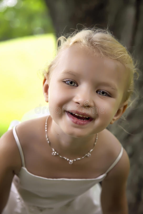 Happy Child. Cute little girl blue eyed blonde girls smiles at the camera stock photography
