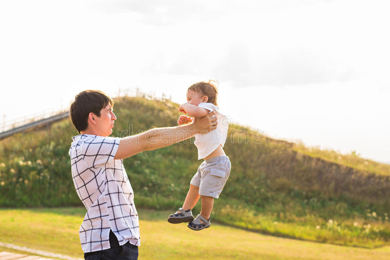Happy child, dad and son having fun, holding on hands on a sunlight sunset background. Family, travel, vacation stock photos