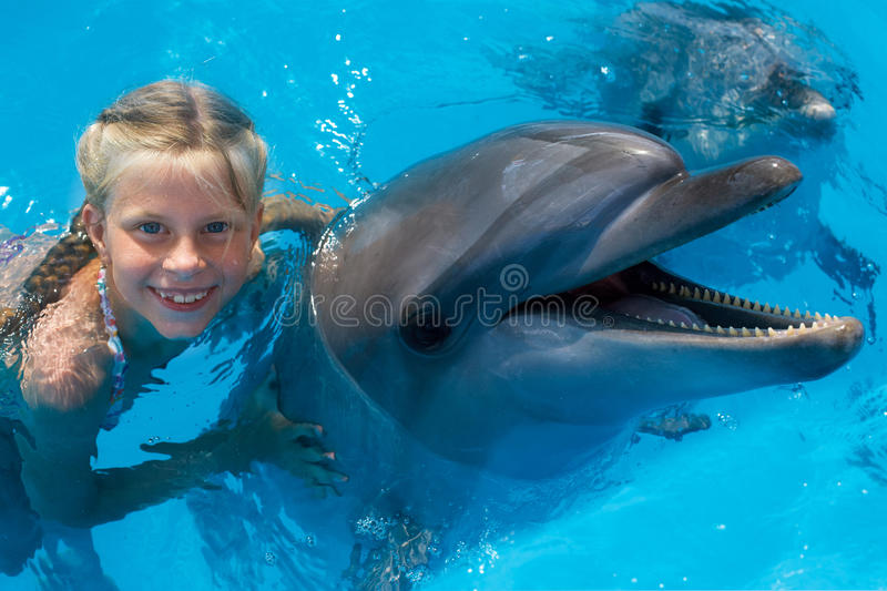 Happy child and dolphins in blue water. royalty free stock photography
