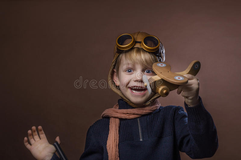 Happy child dressed in pilot hat and glasses. Kid playing with wooden toy airplane. Dream and freedom concept. Retro toned. Studio portrait over brown royalty free stock image