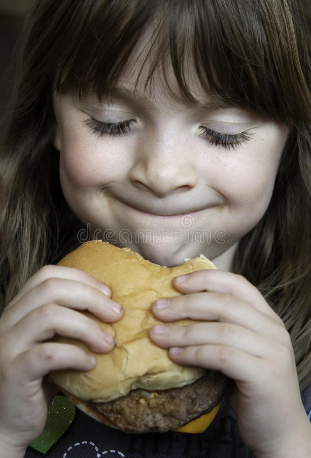 Happy child eating a hambuger stock photo