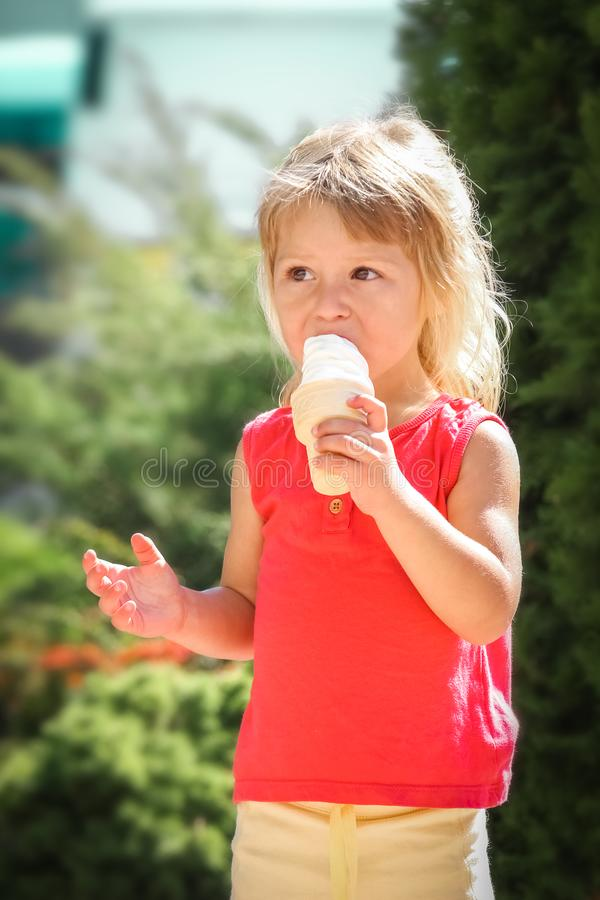 Happy child eating ice cream on the nature of the park stock photo