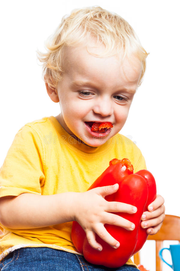 Happy child eating sweet pepper stock photography