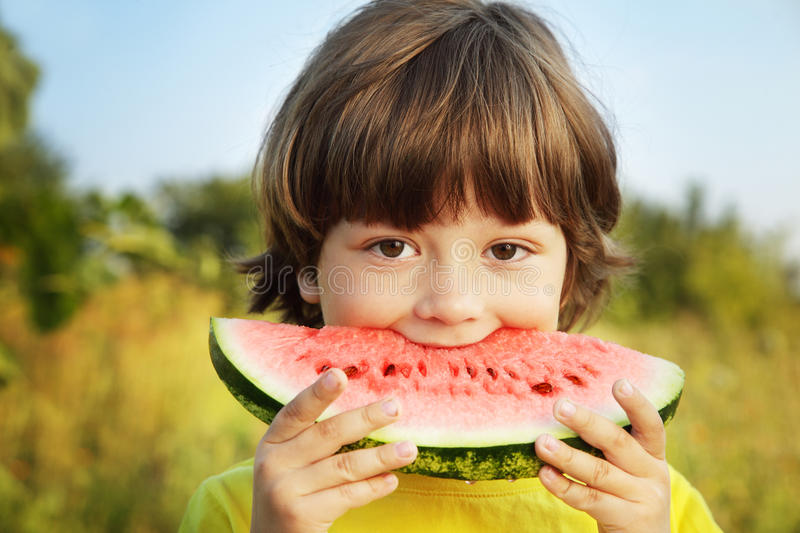 Happy child eating watermelon. In the garden royalty free stock images