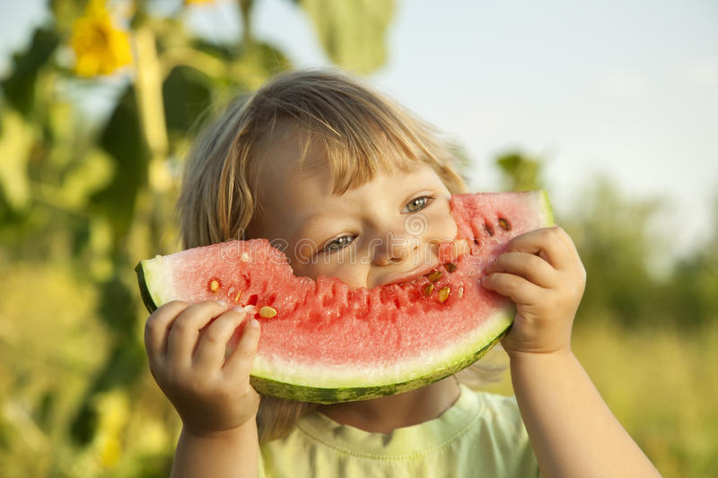 Happy child eating watermelon in the garden stock photo