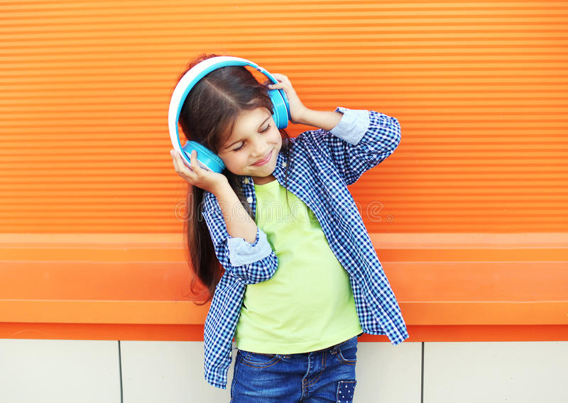 Happy child enjoys listens to music in headphones over colorful orange. Background stock images