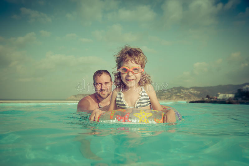 Happy child with father in swimming pool. Summer vacations concept stock image