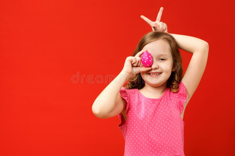 Happy child with fingers makes bunny ears and holds a pink easter egg. Portrait of a little girl on a red background royalty free stock images