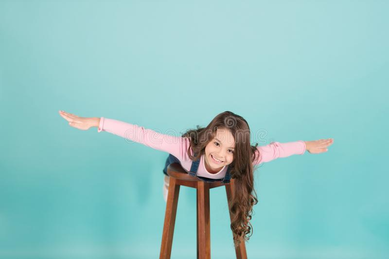 Happy child flying on chair, imagination. Small girl with long hair play pilot, adventure. Imagination, freedom, dream. Adventure, discovery, travel. Fashion royalty free stock photos