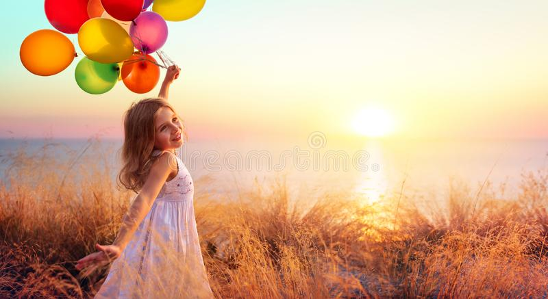 Happy Child In Freedom With Balloons. At Sunset stock image