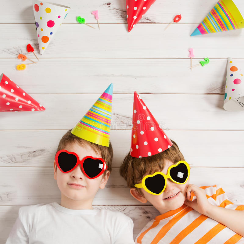 Happy child friend in carnival party, lying on a wooden floor. Happy childhood concept. High top view royalty free stock image