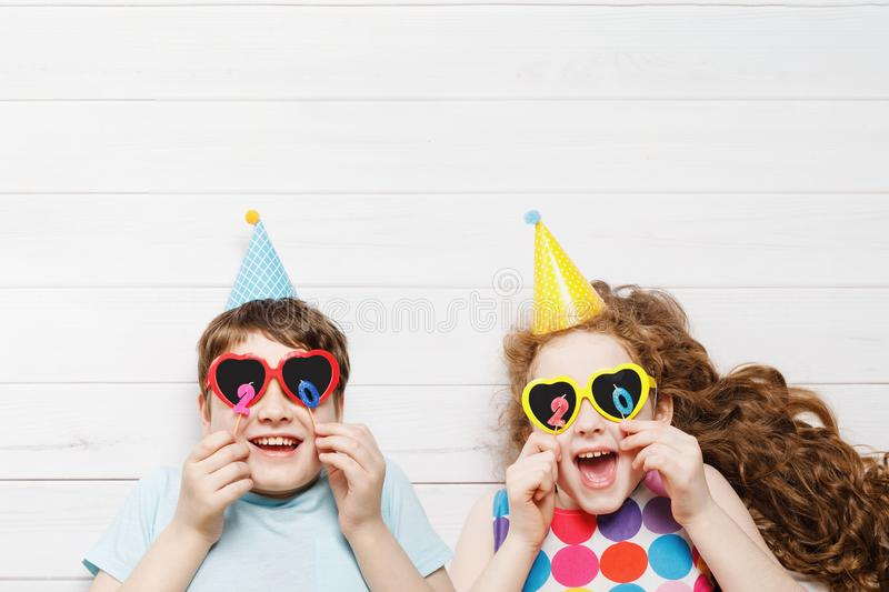 Happy child friend in carnival party, lying on a wooden floor. Happy childhood, holiday 2020 concept. High top view stock photos