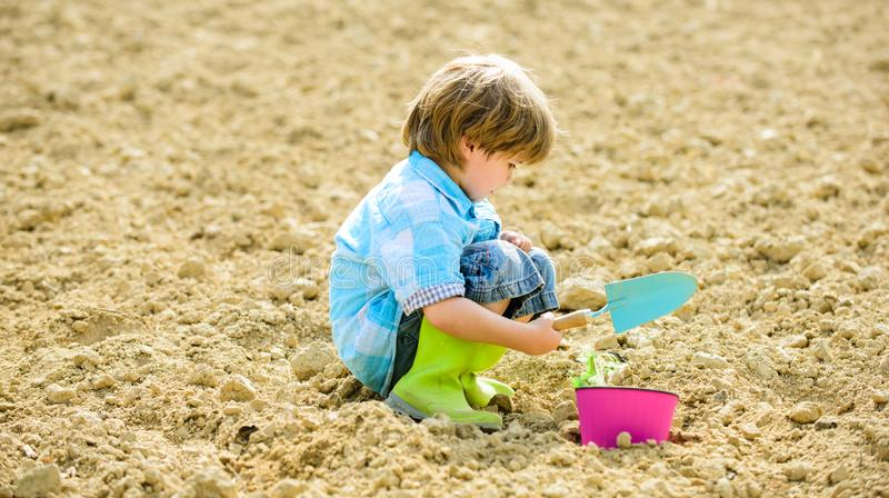 Happy child gardener. botanic worker. Spring. ecology life. Cultivation concept. earth day. new life. summer farm. small. Kid planting a flower. farming and royalty free stock photo