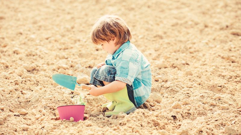 Happy child gardener. botanic worker. Spring. ecology life. Cultivation concept. earth day. new life. summer farm. small. Kid planting a flower. farming and stock photos