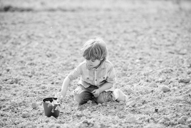 Happy child gardener. botanic worker. Spring season. earth day. new life. summer farm. small kid planting flower. Making. World green. eco farm. human nature stock photography