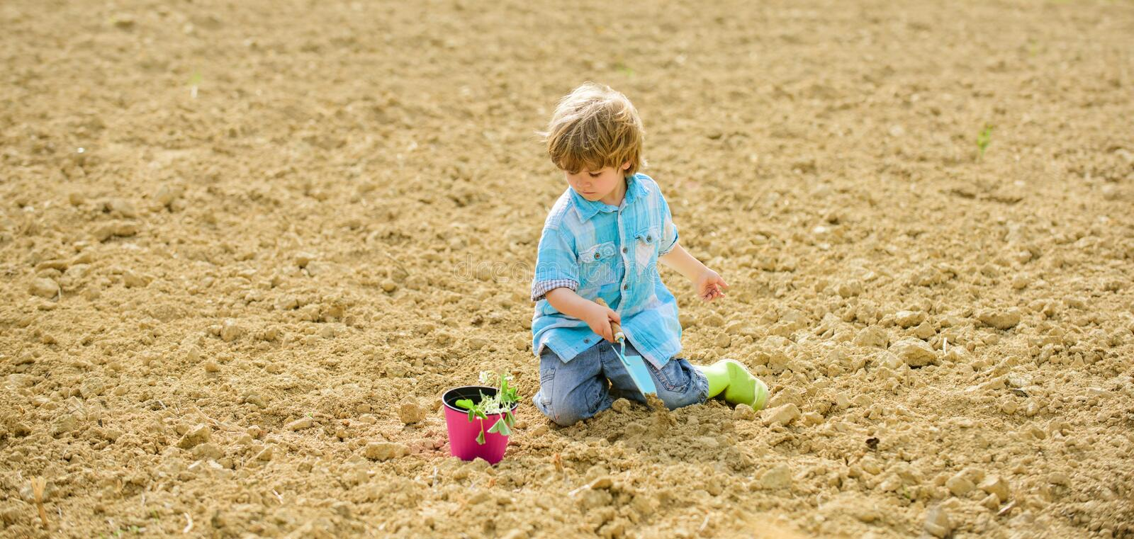 Happy child gardener. botanic worker. Spring season. ecology life. eco farm. human and nature. earth day. new life. Summer farm. small kid planting a flower stock photo