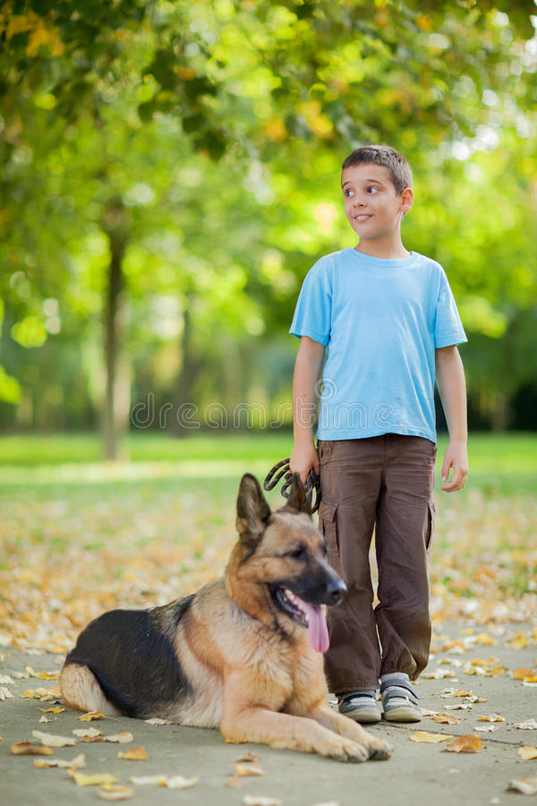 Happy child with a German Shepherd Dog in the park. Young boy with dog in park relaxing happy child with a German Shepherd Dog in the park stock photography