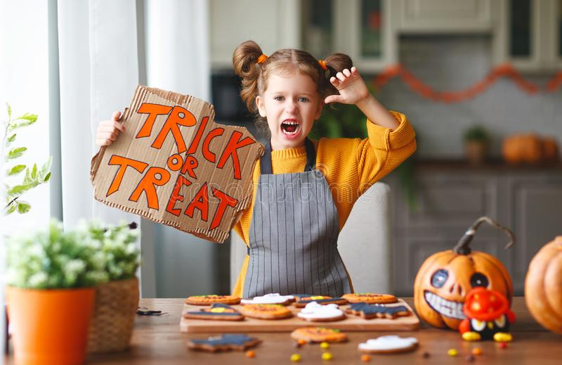 Happy child girl bake cookies and are preparing for Halloween. Happy child girl bake cookies and preparing for holiday Halloween royalty free stock photo