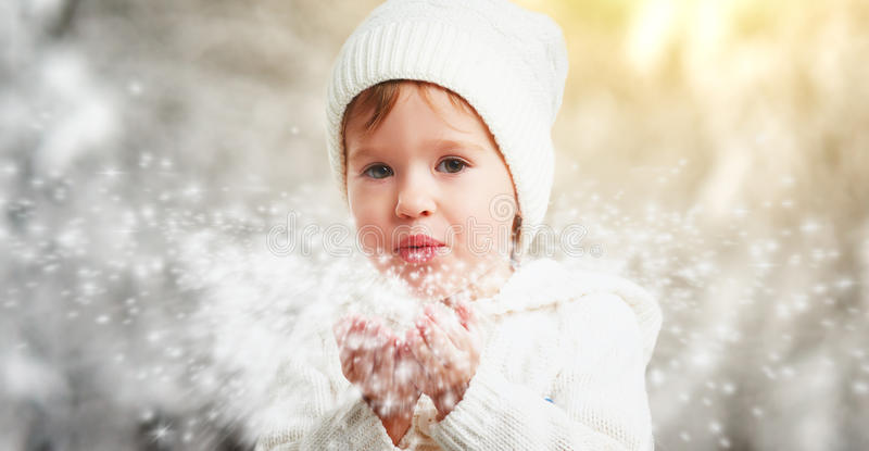 Happy child girl blowing snowflakes in winter outdoors. The happy child girl blowing snowflakes in winter outdoors royalty free stock photo