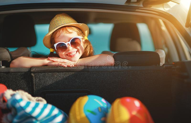 Happy child girl in car going on a summer vacation trip royalty free stock image