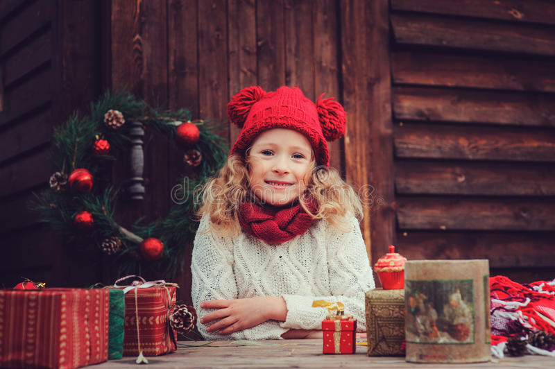 Happy child girl celebrating christmas outdoor at cozy wooden country house with gifts. Happy child girl in red hat celebrating christmas outdoor at cozy wooden stock photo