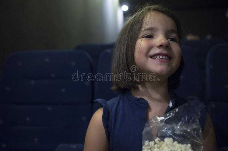 Happy child girl at cinema. Real scene. Child girl watching film at real cinema. She is got a happy expression stock images