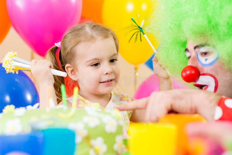 Happy child girl with clown on birthday party. Happy kid girl with clown on birthday party stock photography
