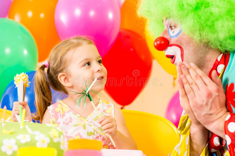 Happy child girl with clown on birthday party. Happy child girl playing with clown on birthday party stock image