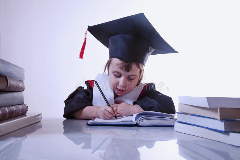 Happy child girl college graduate signing documents. Humorous ph stock photos