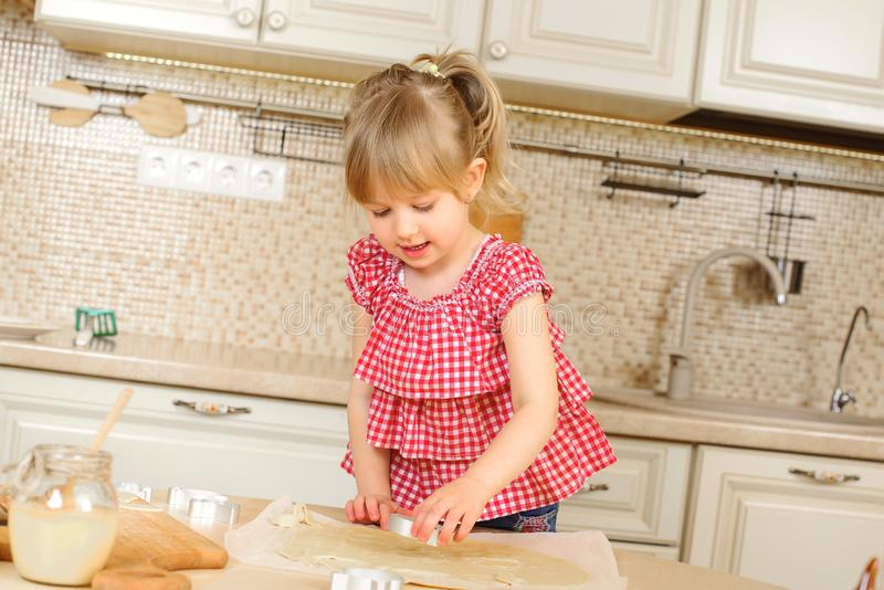 Happy child girl is cooking on kitchen. Child daughter bakes cookies. Happy childhood. Little helper on a kitchen. Lovely family. stock photo