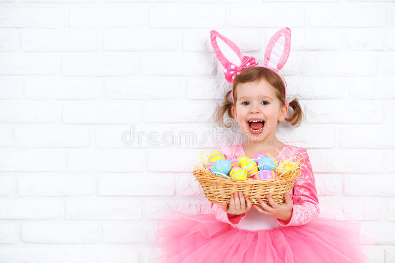 Happy child girl in a costume Easter bunny rabbit with basket of. Happy child girl in a costume Easter bunny rabbit with ears and a basket of eggs royalty free stock photo