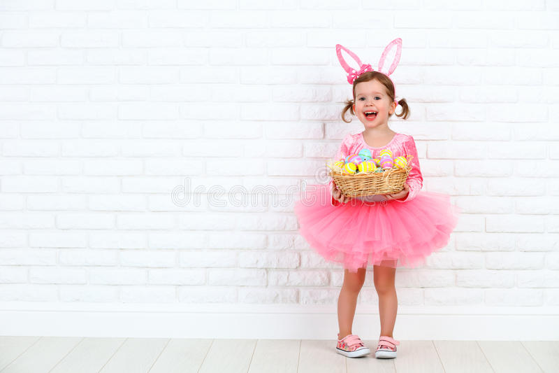 Happy child girl in a costume Easter bunny rabbit with basket of. Happy child girl in a costume Easter bunny rabbit with ears and a basket of eggs royalty free stock photos