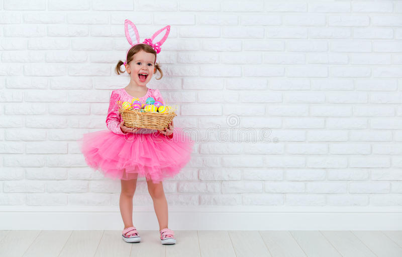 Happy child girl in a costume Easter bunny rabbit with basket of. Happy child girl in a costume Easter bunny rabbit with ears and a basket of eggs stock photos