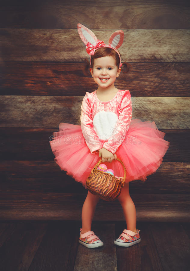 Happy child girl in costume Easter bunny rabbit with basket eggs. Happy child girl in a costume Easter bunny rabbit with basket eggs on wooden background stock photography