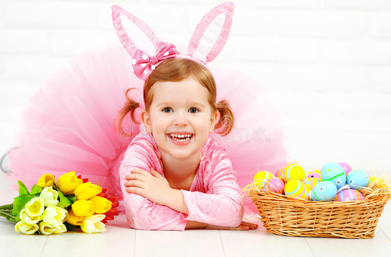 Happy child girl in costume Easter bunny rabbit with eggs and f. Happy child girl in a costume Easter bunny rabbit with basket of eggs and flowers tulips stock image