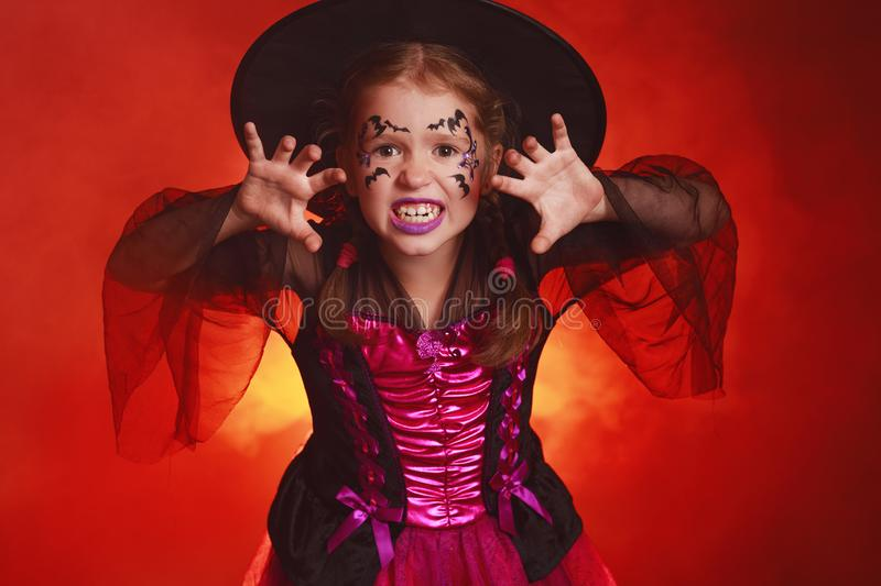 Happy child girl in costumes of witch  in dark red background in halloween. Happy child  girl in costumes of witch in a dark red background in   holiday stock photo