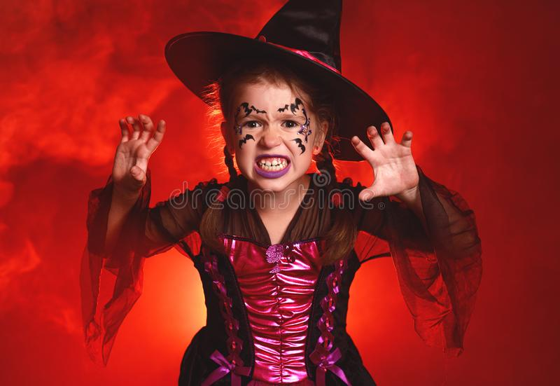 Happy child girl in costumes of witch  in dark red background in halloween royalty free stock photos