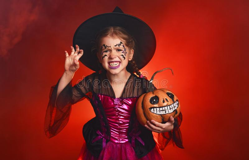 Happy child girl in costumes of witch  in dark red background in halloween stock image