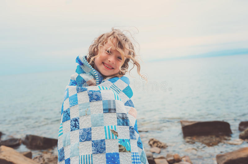 Happy child girl covered in quilt blanket, cozy summer holidays on seaside. Happy child girl having fun covered in quilt blanket, cozy summer holidays on seaside stock photography