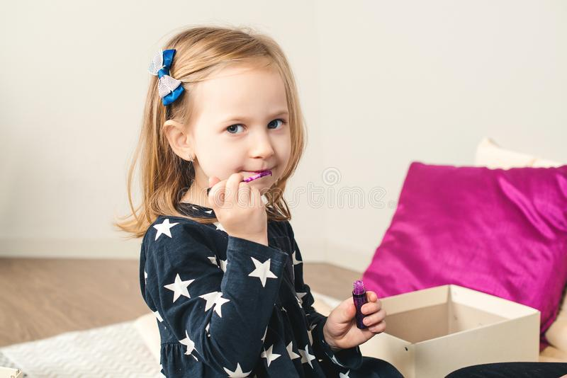 Happy child girl doing makeup and laughing at home. Little daughter painting lips. Kids fashion. Stylish baby girl plays with stock photos