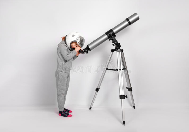 Happy child girl dressed in an astronaut costume looks through a big telescope stock image