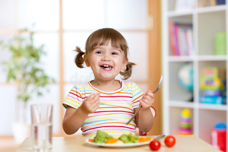 Happy child girl eating vegetables. Healthy nutrition for kids royalty free stock photo