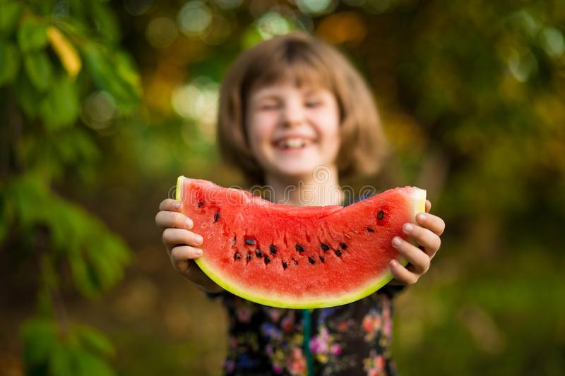 Happy child girl eats watermelon in summer stock images