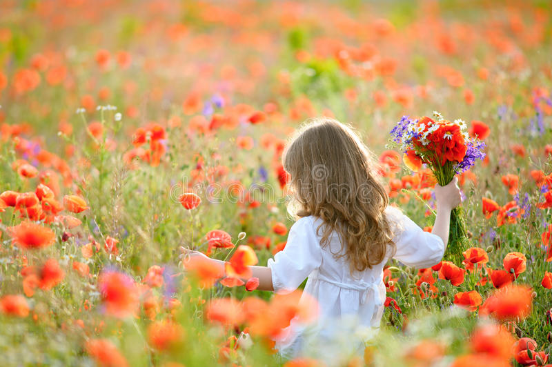 Happy child girl with field flowers running on meadow in summer royalty free stock images