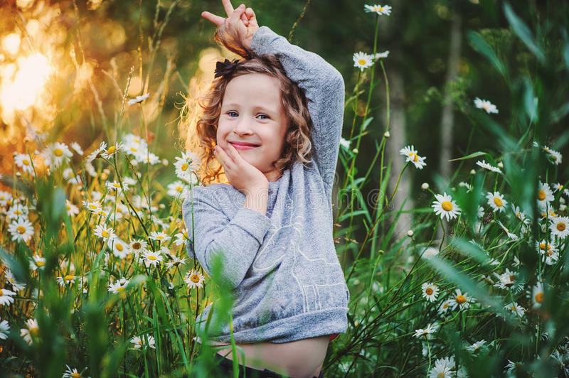 Happy child girl fooling on summer field with flowers. Happy curly child girl fooling on summer field with flowers stock photography