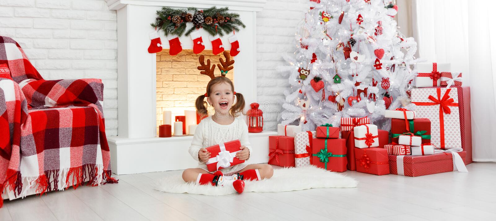 Happy child girl with gift in morning at Christmas tree. Happy laughing child girl with gift in morning at Christmas tree stock image