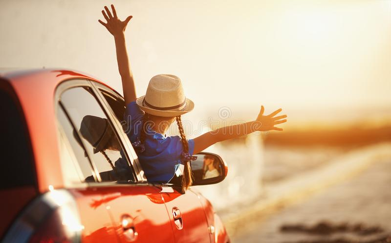Happy child girl goes to summer travel trip in car royalty free stock images
