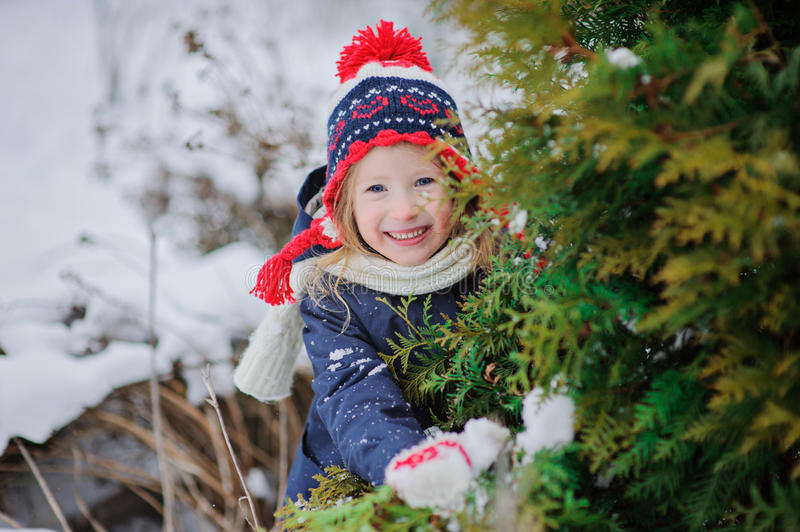 Happy child girl in hat with christmas ornament in winter garden stock image
